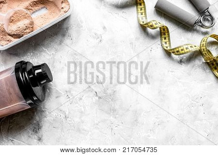 nutrition for workout with protein cocktail powder, measure tape and bars on stone table background top view mockup