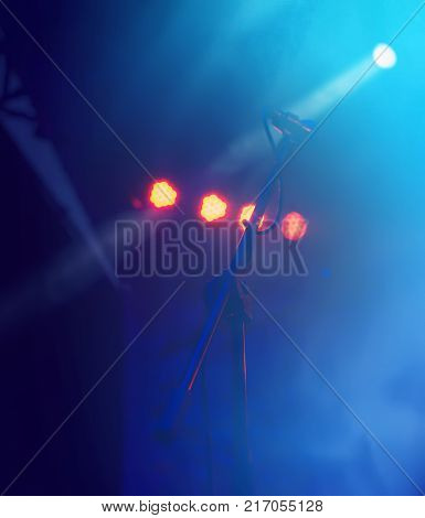 Concert stage. Beautiful Colourful disco lighting in the stage. Performance moving lighting. Concert Light Show. Stage Lights. Microphone.