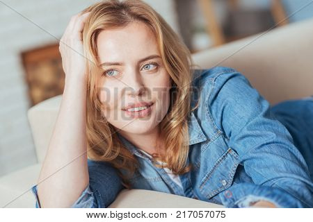 Thoughtful beauty. Charming beautiful young woman looking calm and thoughtful while relaxing on a sofa with her hand touching the head and looking into the distance