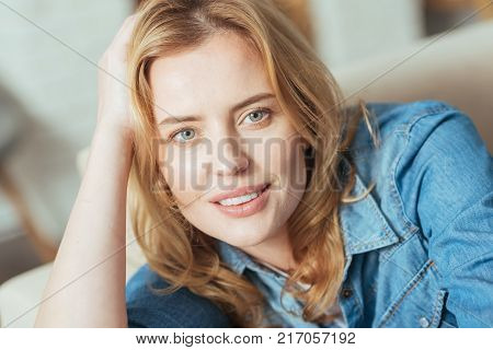 Kind smile. Beautiful calm young woman looking peaceful while resting at home on a comfortable sofa with her hand being on her head
