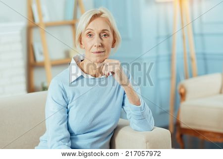 Pleasant pensioner. Calm pleasant aged woman feeling good while sitting in her comfortable room with her fingers touching the chin and waiting for her dear relatives to come