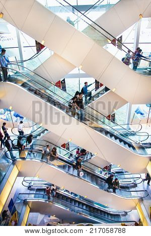 HONG KONG- APR 2. 2016 : People on escalators of shopping mall Peak Tower, landmark and icon of Hong Kong on Apr 2, 2016. On background Victoria Harbour cityscape on sunny day.
