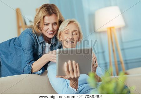 Interesting activity. Calm polite cheerful young woman pointing to the screen of a tablet while teaching her progressive clever grandmother how to use this convenient device