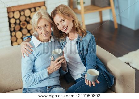 Happy relatives. Pleasant young kind woman softly hugging her aged cute grandmother while sitting on a sofa and drinking tasty tea