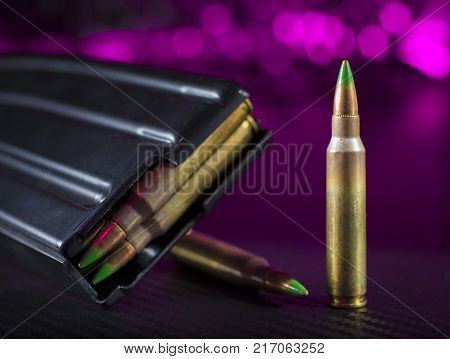 Magazine and green tipped AR-15 cartridge on a purple background