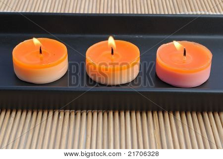 orange candles in black dish on bamboo
