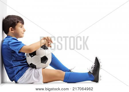 Pensive little footballer sitting on the floor and leaning against a wall isolated on white background