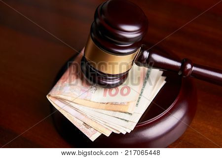 Judges gavel, law mallet or auctioneer's hammer and money stack on wooden table background, Corruption and financial crime theme. Concept of auction, close-up