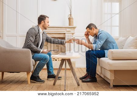 Sad moments. Experienced psychologist giving glass of water to the unsettled male patient who sitting on the couch and looking down