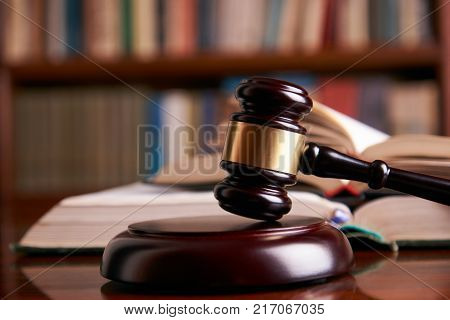 Law gavel or judge mallet on a wooden desk, law books background. Education and legal law concept