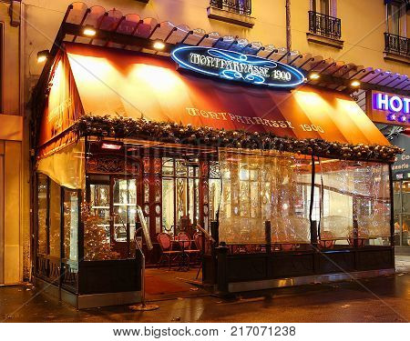 Paris, France -December 03, 2017: Typical Parisian cafe Montparnasse decorated for Christmas in the heart of Paris. Christmas is one of the main Catholic holidays, which is celebrated on a large scale throughout
