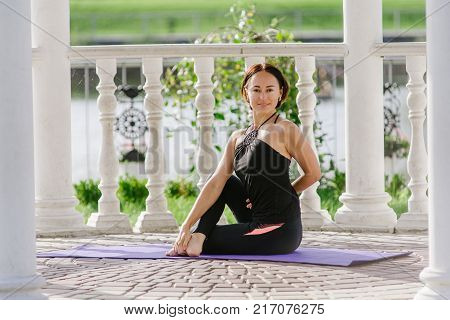 young woman doing yoga in summerhouse in summer