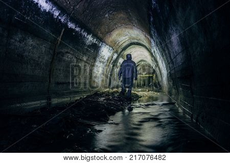 Sewer tunnel worker in special chemical protective suite in underground gassy sewer tunnel