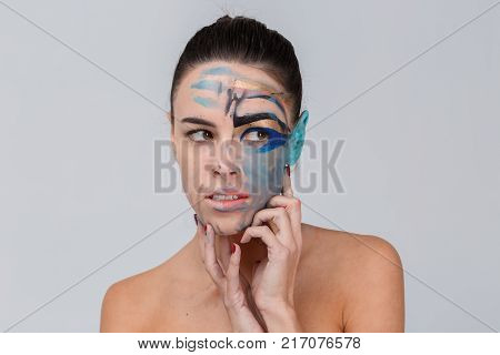 Close-up of a brunette, in the studio, with bare shoulders, with smeared geometric make-up, blue ear, make-up concept, hands folded at the chin, looks away.