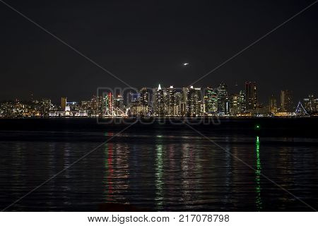 View of metro San Diego from Shelter Island at night with reflection of lights in the water