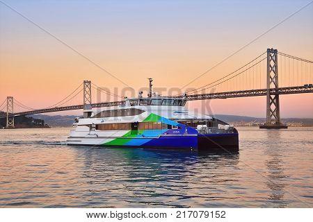 SAN FRANCISCO, CALIFORNIA, USA - OCTOBER 26, 2017: San Francisco ferry and Oakland Bay Bridge in the evening