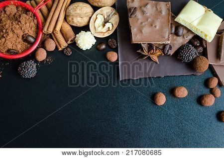 Different kind of chocolate: dark milk porous bars with candies nuts cinnamon anise and cocoa powder on black background. Top view. Copy space.