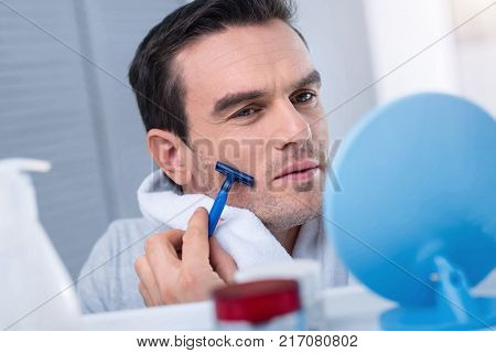 Morning stuff. Brunette charming earnest man trimming his bristles while holding tower and pressing razor against the chick