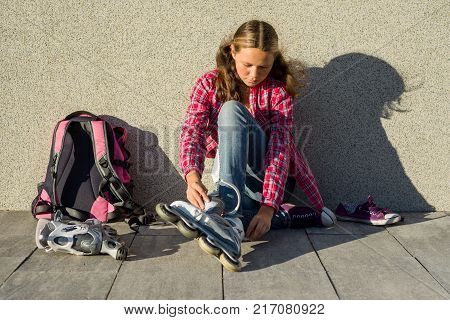 Girl teen removes sneakers and clothes roller skates outdoor. Sits on a wall background, next to her backpack