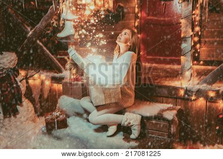 Pretty child girl sits on the porch of a house decorated for Christmas and opens a gift box and surprises. Time for miracles.