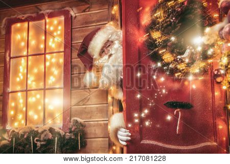 Christmas concept. Portrait of a fairytale Santa Claus peek out from behind the door and wonders. Beautiful house decorated for Christmas. Time of miracles.