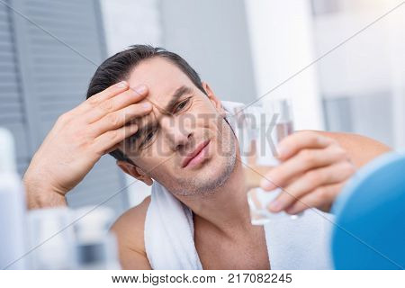 Horrible ache. Disappointed unsatisfied uneasy man looking at the glass of water  which he holding and touching his forehead