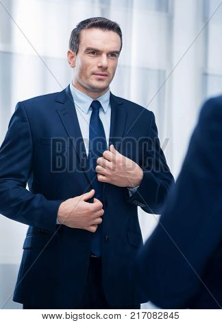 Moral challenge. Irresistible handsome young man touching jacket while standing right and preparing morally