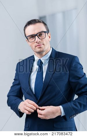 Office style.  Handsome elegant earnest man touching his jacket while wearing glasses and looking straight