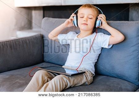 Relaxing music. Nice delighted peaceful boy sitting on the sofa and closing his eyes while listening to the relaxing music