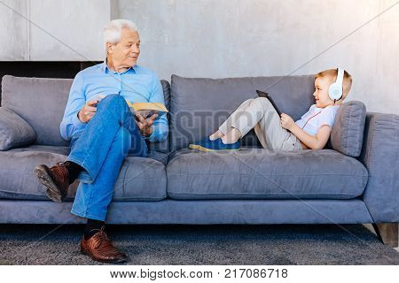 My grandfather. Nice pleasant young woman lying on the sofa and holding a tablet while spending time with his grandfather
