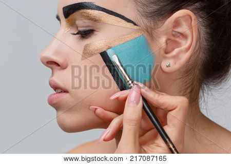 The hand of the make-up artist paints with a brush, the blue paint on the girl's face, in the studio, the concept of geometric make-up, the girl with her eyes closed.