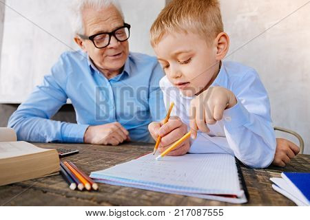 Time for studying. Positive nice smart grandfather sitting at the desk and helping his grandson with studying while caring about him
