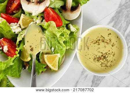 Ceramic bowls with ranch dressing and fresh salad on light background