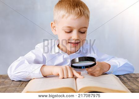Interesting thing. Positive nice cute boy sitting at the table and holding magnifying glass while reading a book