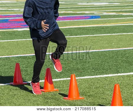 A high school track and field sprinter performs running drills over orange cones on a green turf field.