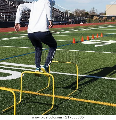 A high school track and field runner is jumping over hurdles during jumps practice on a turf field.