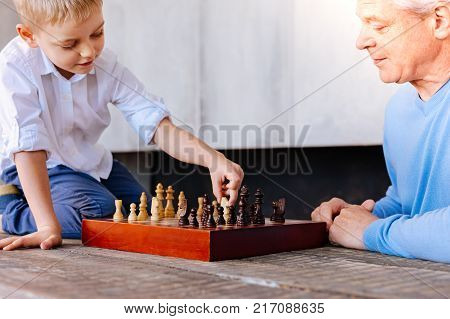 Grandfather and grandson. Joyful nice cute boy holding a chess piece and making his move while playing with his grandfather