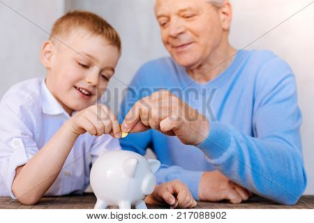 Saving money. Delighted nice pleasant boy sitting together with grandfather and holding a coin while putting it into the money box
