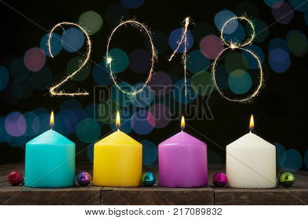 Multicolored burning candles with bokeh and digits 2018 on black background.Concept of New Year and Xmas