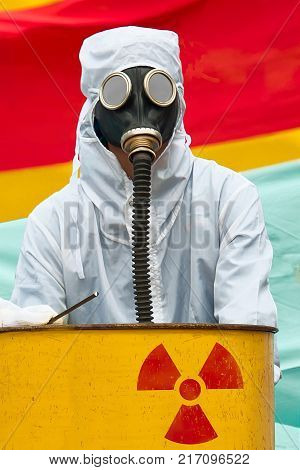 A man in bio-hazard suit standing behind a rusty tank with nuclear symbol screened on. He is wearing a gas mask with flexible rubber breathing tube