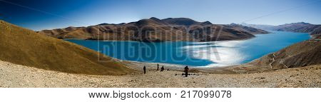 Panoramic view of Tibet natural landscape - blue azure water lake surrounded desert mountains. Yamdrok Lake (Yamdrok Yumtso Yamzho Yumco) is a sacred lake in Tibet.