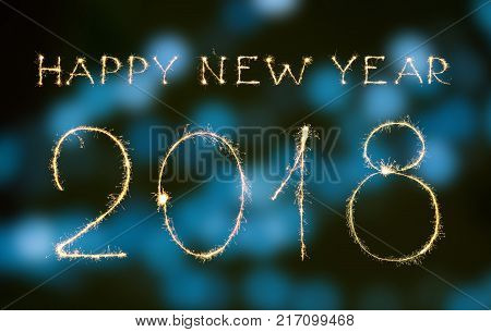 Happy new year and digits 2018 written with sparklers and bokeh isolated on black