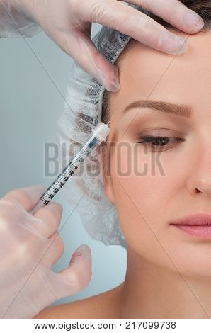 Woman is getting filler injection over eyebrow. Anti-aging treatment and face lift. Plastic Surgery