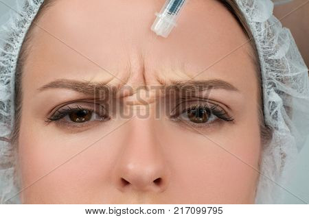 Woman is getting injection. Anti-aging treatment and face lift. Cosmetic Treatment. Facial skin lifting injection to woman's face. Plastic Surgery
