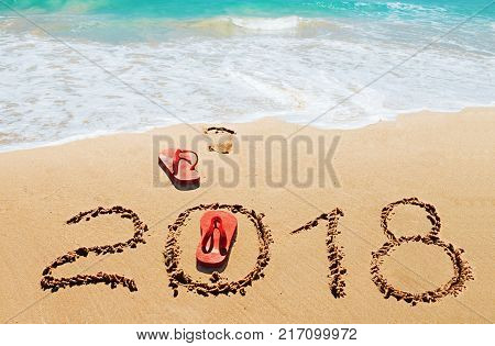 Red flip flops and digits 2018 on the beach sand.Concept of summer vacations new year and Christmas