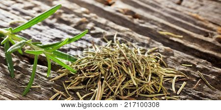 Closeup of dry and fresh rosemary in daylight placed on an old wooden surface. Space for text.