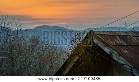 Old house with rusted tin roof with sun setting behind mountains bouncing off the atmosphere and smoke from chimney in background