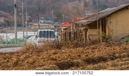 White truck parked next to an old run down abandoned shack with red roof house and small community in rural setting