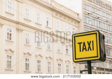 A modern taxi information sign on the background of houses in a European city.