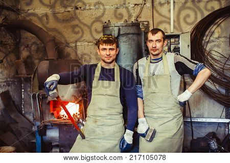 two forge are in working clothes in the forge